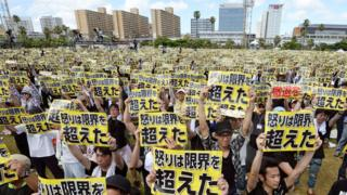 """Protesters raise placards reading """"Anger was over the limit"""" during a rally against the U.S. military presence on the island"""