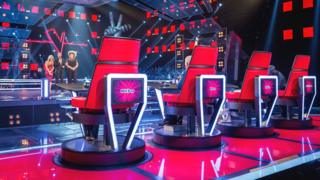 The Voice Coaches behind their chairs