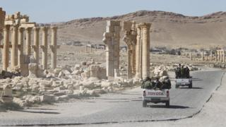 الجيش السوري يمر بجانب قوس النصر في مدينة تدمر في أبريل/نيسان
