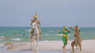 A still from the vide showing the characters on the beach, with one on a horse