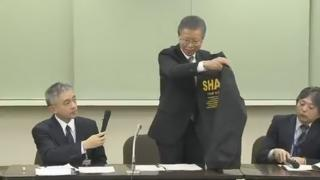 An official holding up one of the jackets