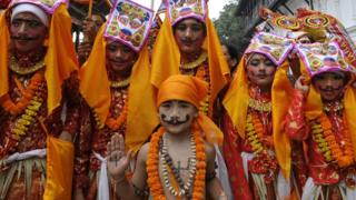 Children dressed in orange, with large moustaches and pictures of cows positioned on their heads.