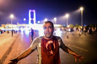 A man covered with blood stands near the Bosphorus bridge as Turkish military clash with people at the entrance to the bridge in Istanbul on 16 July 2016