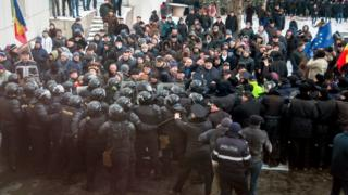 Protesters push a riot police line outside the parliament building in Chisinau, Moldova
