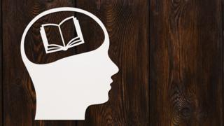 Dibujo de un figura humana con un libro en la cabeza.