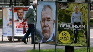A man walks between posters of Norbert Hofer (left) and Alexander Van der Bellen in Vienna, 19 May
