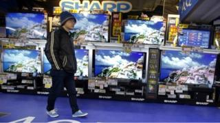 "A shopper walks in front of Sharp""s Aquos flat-panel TVs at an electronics store in Tokyo, Thursday, Feb. 25, 2016"