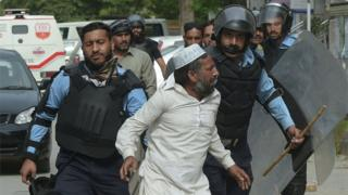 Pakistani riot policemen arrest a supporter of executed Islamist Mumtaz Qadri during an anti-government protest near the parliament building in Islamabad on March 28, 2016.