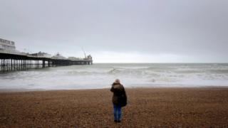 a woman watches the sea on the beach at Brighton