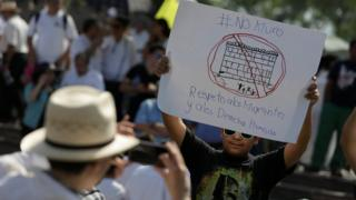 """A demonstrator holds a placard reading: """"No wall. Respect to immigrants and human rights"""" during a protest against U.S. President Donald Trump's proposed border wall and to call for unity, in Monterrey, Mexico, on 12 February"""