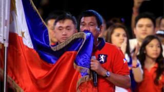 Rodrigo Duterte kisses a Philippines flag in Manila (7 May 2016)