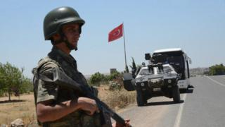 A Turkish soldier stands guard at a border crossing with Syria