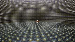 workers on an inflatable raft inside a huge neutrino observatory