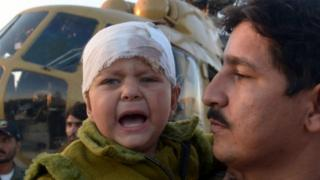 A Pakistani army officer carries a young injured earthquake survivor who was evacuated from Chitral by military helicopter to a base in Peshawar (27 October 2015)
