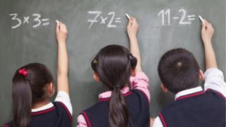 Children write sums on a blackboard