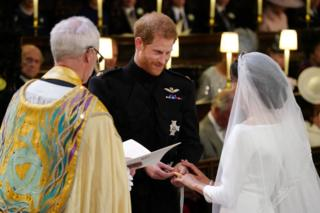 Prince Harry places the wedding ring on the finger of Meghan Markle in St George's Chapel