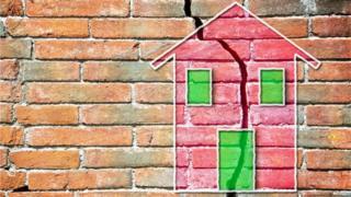 Un dibujo de una casa sobre una pared de ladrillos con una grieta enorme