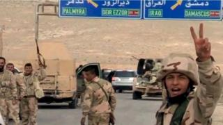 "Forces loyal to Syria""s President Bashar al-Assad gesture as they advance into the historic city of Palmyra in this picture provided by SANA on March 24"