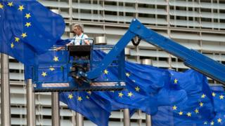 A worker on a lift adjusts the EU flags in front of EU headquarters in Brussels (June 22, 2016)