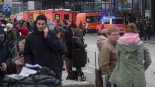 Travellers wait outside the Hamburg, northern Germany, airport Sunday, 12 February 2017 after after several people were injured by an unknown toxic that likely spread through the airport's air conditioning system