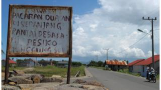 "A motorist rides past a board that, in the local language, reads ""If you date on the beach, the risk is on your own"" in Banda Aceh"