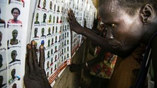 A woman looking at wall of pictures to identify missing loved ones