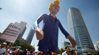 A woman carries an effigy of US President Donald Trump during a march in Mexico City against the proposed border wall, 12 February 2017