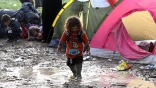 A girl plays in the mud in a tent camp near the village of Idomeni, on 1 March, 2016 as migrants and refugees walk to cross the Greece-Macedonia border.