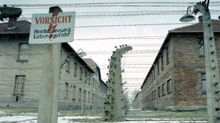 Barbed wire fence around prisoner barracks at former Auschwitz-Birkenau death camp - file pic