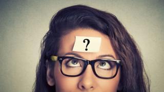 Mujer con un papel con un signo de interrogación en la frente