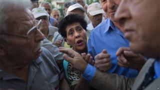 Pensioners argue with a bank employee as they wait for the opening of the national bank of Greece to withdraw a maximum of 120 euros ($134) for the week in central Athens on 16 June