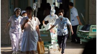 Hospital staff rushing to treat a victim of the Kunshan car parts factory disaster