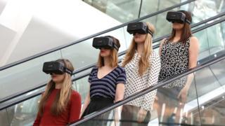 Mujeres en escaleras mecánicas con cascos de realidad virtual.