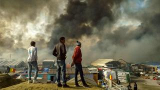 """Migrants stand on a hill overlooking the """"Jungle"""" migrant camp in Calais, northern France, as smoke rises on October 26, 2016"""