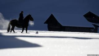 A rider and her horse are silhouetted as they make their way through snow