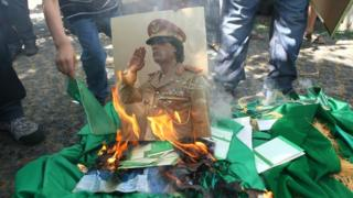 A photo of Muammar Gaddafi is destroyed in 2011