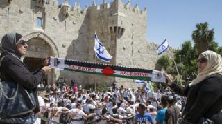 Palestinian women hold Palestine scarf as Israelis