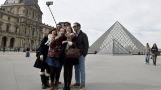 Tourists use a selfie stick outside the Louvre