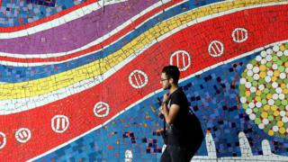 An Iranian man walks past a mural on a street in the capital Tehran