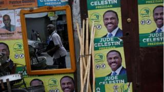 A man can bee seen looking at posters of presidential candidate Jude Celestin of LAPEH (Alternative League for Progress and Emancipation of Haiti) on a wall