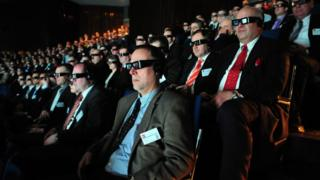 An audience watches a 3D movie