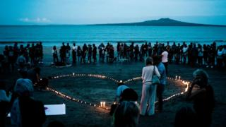 A vigil on a beach in Auckland with people standing around a heart-shape made from candles