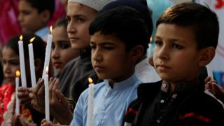 Pakistani school children light candles and pray to mark the second anniversary of terrorists attack on Army Public School attack in Peshawar, Pakistan, 16 December 2016