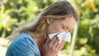 A woman holding a tissue to her nose