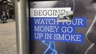 "An anti-begging poster which says ""Begging: Watch your money go up in smoke"""