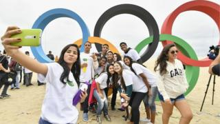 People taking selfies with Olympic rings on a beach in Rio