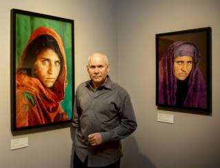 """US photographer Steve McCurry poses next to his photos of the """"Afghan Girl"""" Sharbat Gula in Hamburg, Germany on June 27, 2013."""