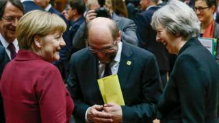Theresa May shares a joke with German Chancellor Angela Merkel and European Parliament president Martin Schulz