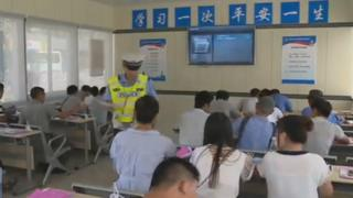 A view of a police officer inside the classroom with people sitting at desks