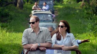 The Duke and Duchess of Cambridge standing up on the back of a jeep